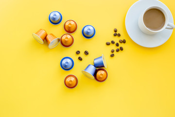Keuken foto achterwand Cafe Beverage capsules for coffee mashine near coffee cup and grains on yellow background top view copyspace