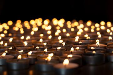 Flaming candles. Spiritual image of tealights providing sacred light. Romantic candlelight at night.