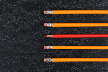 yellow pencils and one red pencil on blackboard