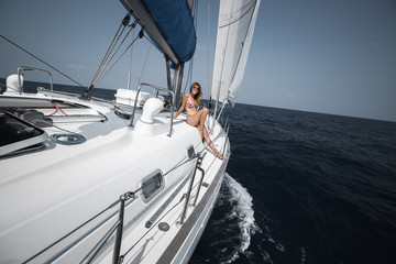 Young woman sits on deck of the sailing boat moving in an open tropical sea under the sails
