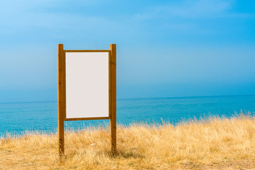 Beautiful view of water, sky and horizon and a large sign with copy space in the foreground.