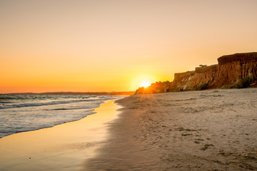 Beautiful colorful sunset in Algarve Portugal. Peaceful beach water and cliffs.