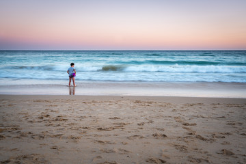 Long exposure image of young girl standing on a beach with waves, sunset in Portugal.