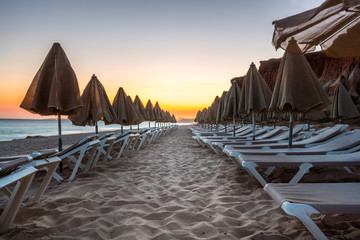 Beautiful sunset in Algarve Portugal.  Beach and cliffs with closed sun umbrellas and sunbeds.