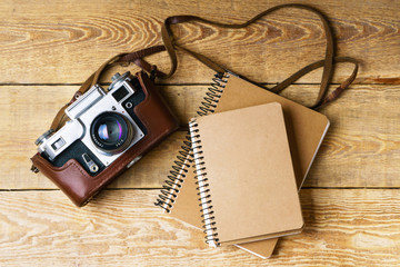 Old retro camera,  spiral blank kraft paper notepad on vintage rustic wooden planks boards. Education photography courses back to  school concept abstract background. Close up, top view, copy space.
