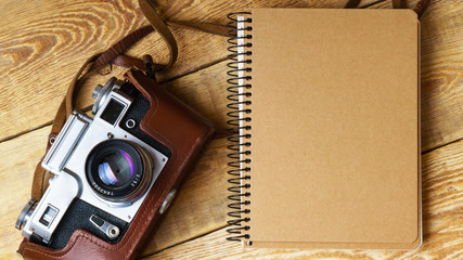Old retro camera,  spiral blank kraft paper notebook on vintage rustic wooden planks boards. Education photography courses back to  school concept abstract background. Close up, top view, horizontal.