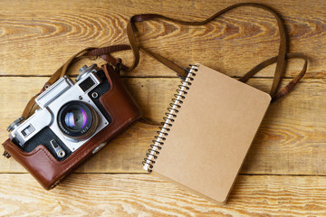 Old retro camera,  spiral blank kraft paper tablet on vintage rustic wooden planks boards. Education photography courses back to  school concept abstract background. Close up, top view, copy space.