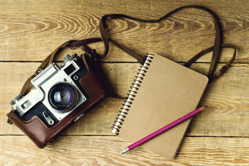 Old retro camera, notebook, pencil on vintage rustic wooden planks boards. Education photography courses back to  school concept abstract background. Close up, top view, copy space, toned.