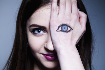 Staring brunette woman with painted eyes  on her hand. Artwork.