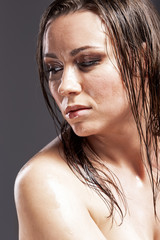 Portrait of Sensual Tanned Caucasian Brunette Woman With Sad Expression with Wet and Shining Skin and Wet Hair. Against Dark Grey Background.