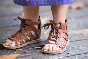 Baby, kid, girl feet in brown, leather sandals