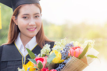 Asian woman graduated with cap and gown smile and holding bouquet in her hand