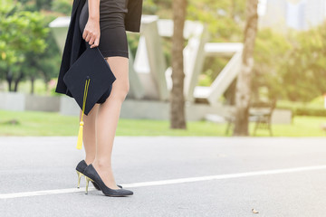 back of view Graduate woman holding cap and gown walking on the road