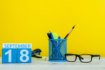 18th September. Image of september 18, calendar on yellow background with office supplies. Fall, autumn time