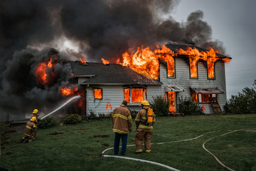 Fire Fighters Putting Out A House Fire Fotomurales