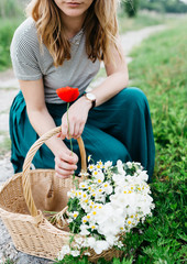 Blonde woman in the nature holding a bunch of flowers