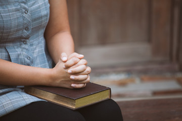 Woman hands folded in prayer on a Holy Bible  for faith concept in vintage color tone