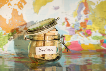 Travel money savings in a glass jar with map in background