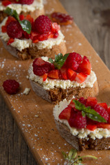 Fruit brusquest with raspberry and cottage cheese on a wooden board