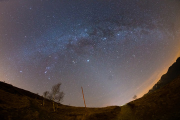 The starry sky and Milky Way captured on the Alps by fisheye lens with scenic distortion and 180 degree view. Andromeda, The Pleiades, Orion and Sirio clearly visible. Low digital noise.