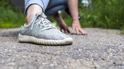 Legs in the sneakers of a young girl on the road