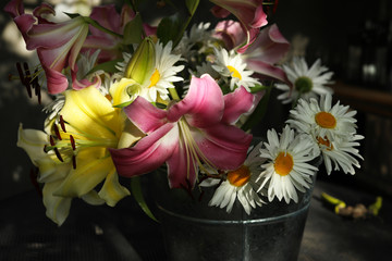 Lilies and chamomiles in a tin can.