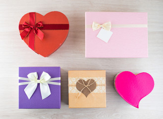plenty assorted colorful and different in the shape and size gift boxes on light wooden background for the celebration of different holidays, flat lay