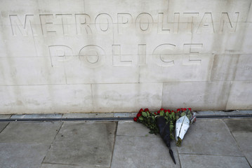 Flowers are left outside New Scotland Yard after a minute's silence the morning after an attack by a man driving a car and wielding a knife left five people dead and dozens injured, in London