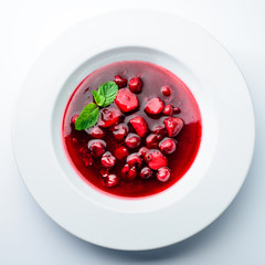 classic Italian food. Beautifully decorated plate with strawberries and raspberries in a ginger juice, dark background, top view