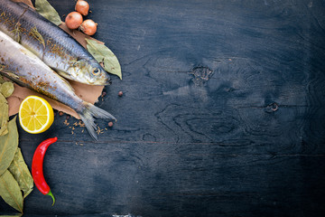 Fresh fish with vegetables, spices and oil. On a black wooden background. Free space for text . Top view