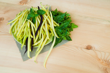 Asparagus bean pods on a plate on a wooden table