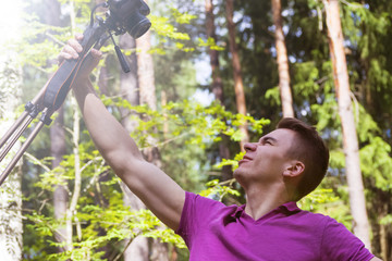 A young man photographs himself with a tripod