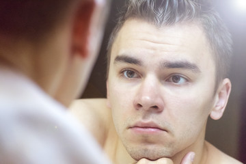 The young man looks at himself in the mirror