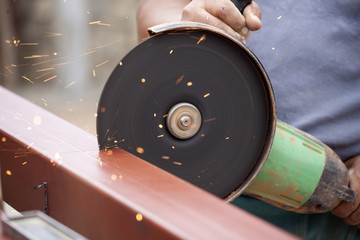 worker cuts a metal pipe with an electric saw
