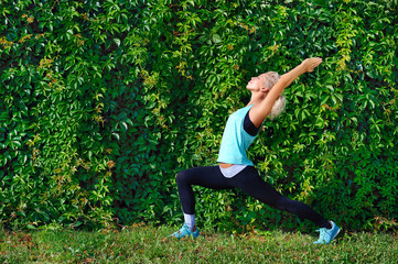 Sportive woman practicing warrior yoga pose standing over green fence