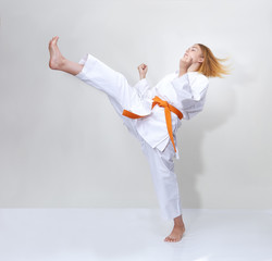 Sportswoman with an orange belt beats a kick on a gray background