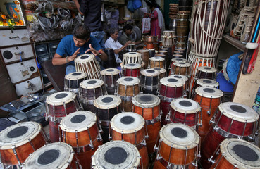 A man checks the sound of a dhol, an Indian musical instrument, inside a workshop in Mumbai