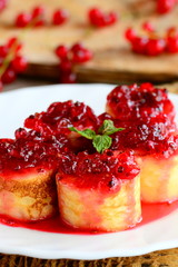 Sweet crepes rolls with redcurrant confiture on a white plate. Little stuffed crepes dessert recipe. Delicious Easter brunch idea. Vertical photo