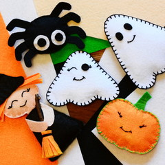 Halloween home decor toys. Felt witch with broom, pumpkin head, two ghosts, spider. Halloween crafts on colored felt sheets. Handmade sewing crafts concept. Top view. Closeup