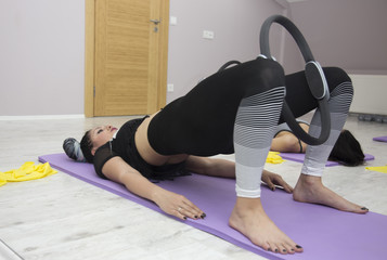 woman ring pilates exersise on foam