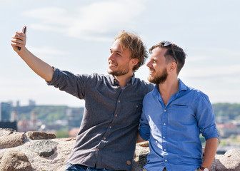 Smiling young caucasian buddies making selfie at city skyline