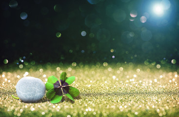 Abstract background with four leaf lucky clover and stone