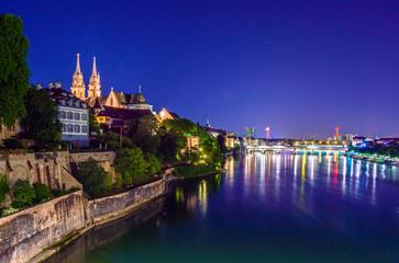 Night view of the Old Town of Basel with red stone Munster cathedral and the Rhine river,...