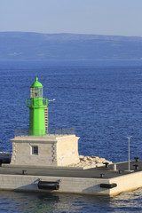 Lighthouse on commercial dock for ships and boats, Photo of green lighthouse on harbor with blue sea in the background