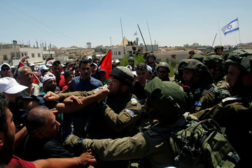 Israeli soldiers scuffle with Palestinians following a protest against building a new Israeli military tower in the West Bank town of Dura, south of Hebron