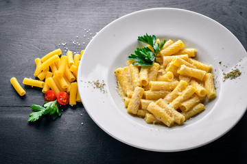 Pasta with cream sauce and parmesan cheese. Italian traditional food. On a wooden background. Top view. Free space for your text.