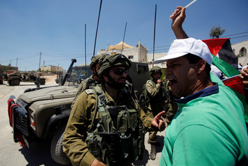 A Palestinian protester shouts in front of Israeli soldiers during a protest against building a new Israeli military tower in the West Bank town of Dura, south of Hebron