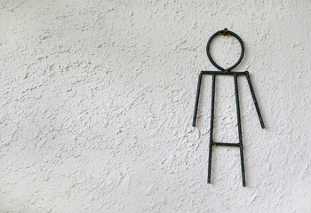 Toilet male signs on the abstract white rough cement wall background.