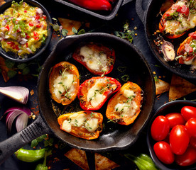 Grilled sweet peppers poppers stuffed with cheese and herbs, mix  delicious appetizers on a black background, top view