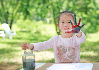 Cute little girl with painted hands in the park, Focus at her face.